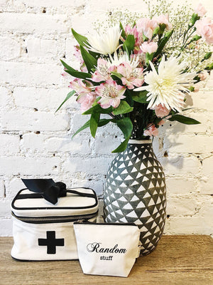 A case with flowers on top of a wood desk with a medical box and random stuff case besides it.
