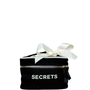 "Mini black beauty box with ""secrets"" across the front and a white bow on the handle."