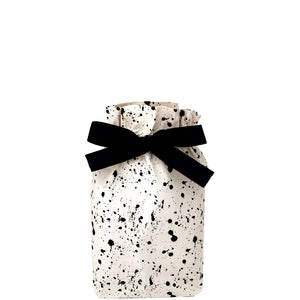 Small reusable gift bag with black splatter paint across it.