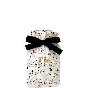 "Small gift bag splattered with ""Tia"" monogrammed on the front."