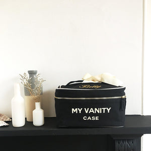"Travel makeup case in black with ""my vanity case"" printed on the front sitting on a shelf."