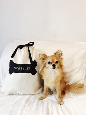 A chihuahua on a bed sitting next to a dog stuff bag.