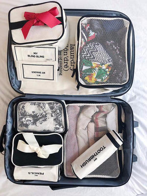 A suitcase packing with toothbrush cases, pencil case and packing cubes.