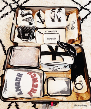 Suitcase filled with personalized packing cubes, charger case, vanity case, laundry bag and more.
