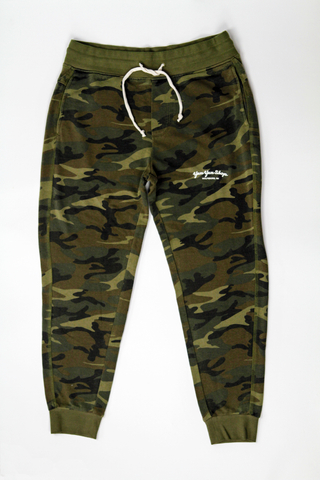 Men's green camo pants with drawstring and Yum Yum Shop printed on the leg.