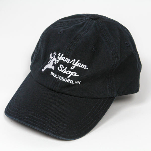 A black ball cap with the Yum Yum Shop logo in white stitching.