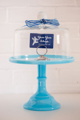 A Yum Yum Shop gift card placed inside a blue and glass cake stand.
