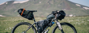 Mountain bike with bags and leather saddle in front of a hill