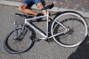 Legs of man lying on the ground under a wrecked bicycle after an accident