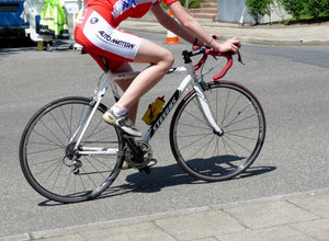 Lower body of cyclist pedaling a road bike on pavement
