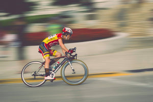Man racing his bicycle by quickly against a blurred background