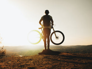 Rear view of a biker holding up his bike while looking into the sun from a hilltop