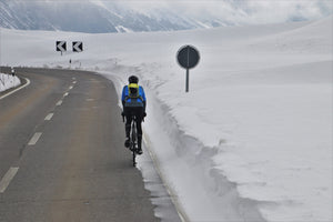Cyclist riding on a highway in winter through snow-covered mountains
