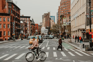 Man riding his bicycle through a busy New York intersection