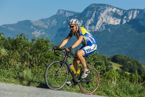 Man cycling up a hill with an pained expression