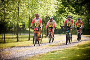 Group of happy mountain bikers riding on a park trail