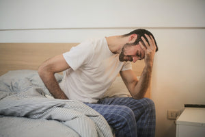 Man sitting up in bed looking distressed because he can't sleep