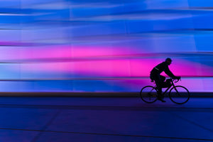 Silhouette of a man cycling in the dark with colored lights on the background wall