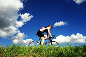 Man cycling below a bright blue sky with a few clouds