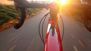 Rider's view over the handlebars on a bicycle descending quickly down a hill toward sunset