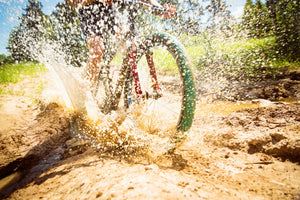 Close-up of cyclist's wheel splashing through mud on a dirt trail