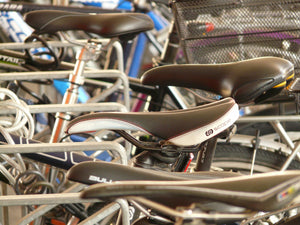 Close-up of different bike saddles on a row of bicycles
