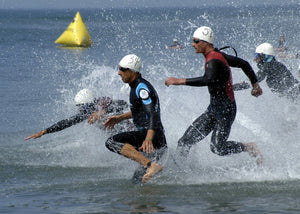 Men diving into open water in a triathlon swim