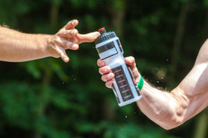 Close-up of two cyclists' hands passing a water bottle between them