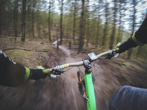 A mountain biker's view of the trail and cycling GPS while riding through the woods