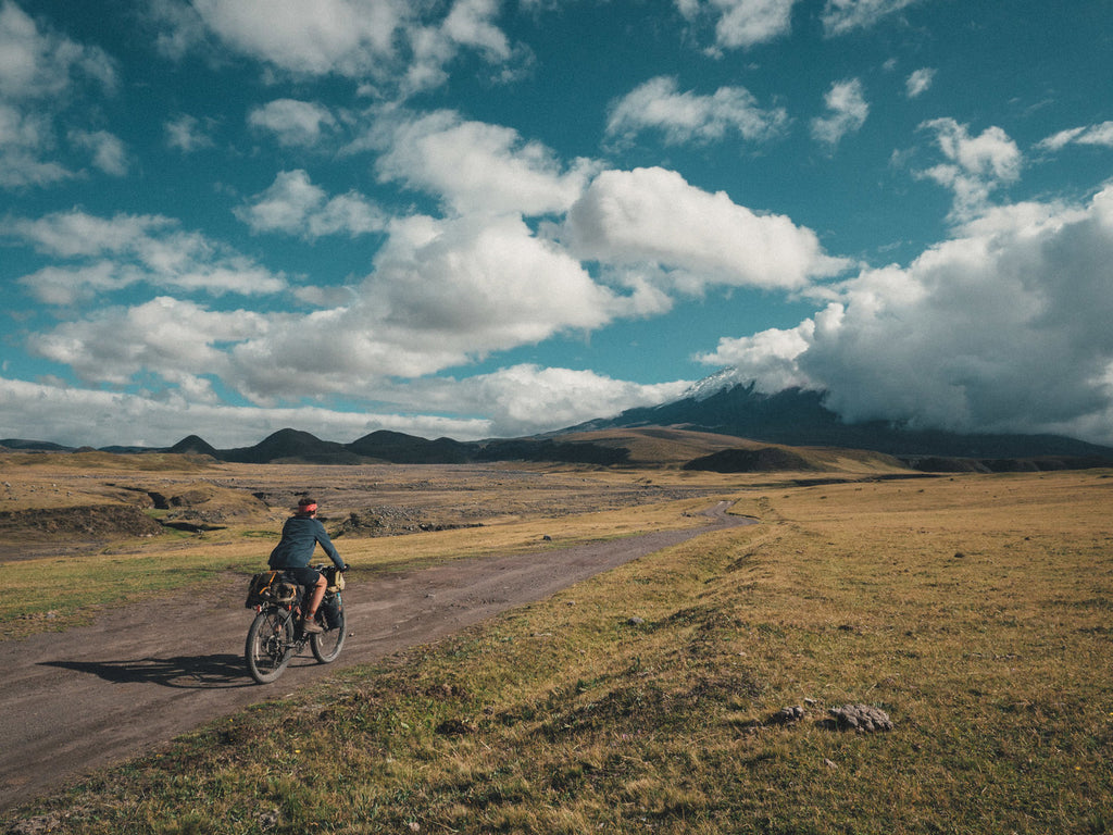 Man biking a trail into the mountains of Cotapaxi, Ecuador