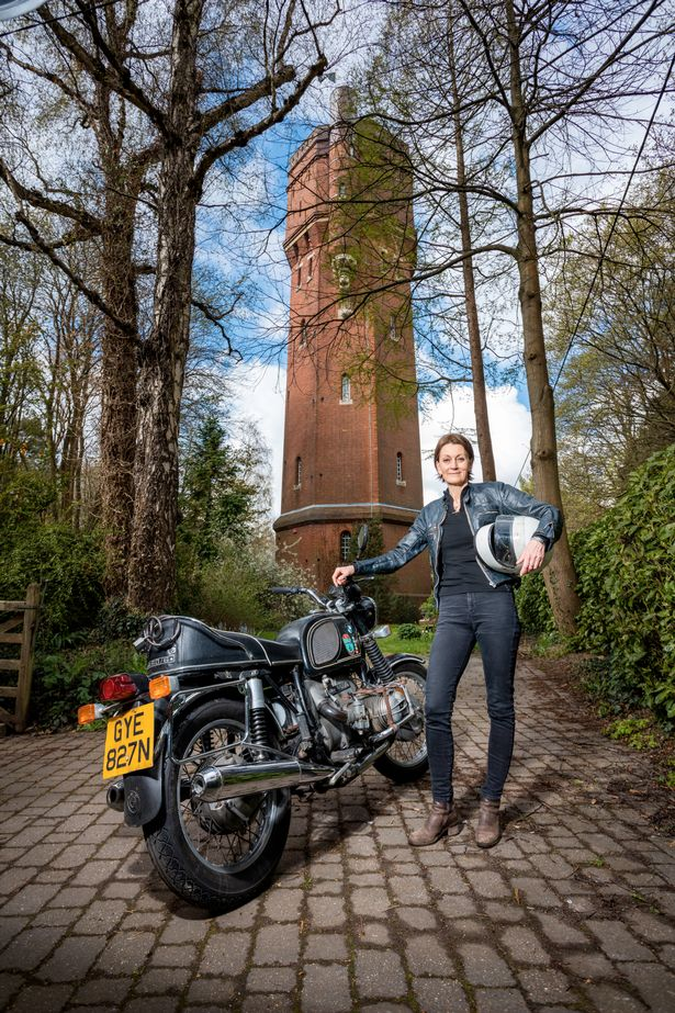 Elspeth Beard with her longtime companion, a 1976 r60/6, in front of a water tower in Godalming, England she converted to her residence.