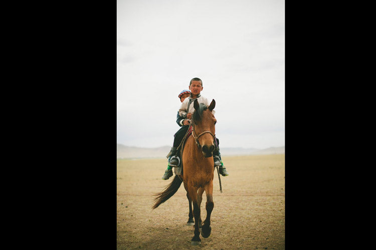 Eating lunch on the steppe I turned around to find these two boys regarding me. The older in front, handled the reins. The younger brother, wearing the stars and stripes hat, handled the horsewhip. Whirling and riding away, the younger boy on back waved shyly over his shoulder.
