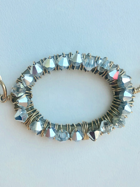 silver swarovski crystals wrapped around an oblong pendant.