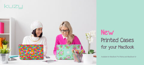 Two-stylish-women-seated-at-a-desk-using-MacBook-Pros-with-designer-cases