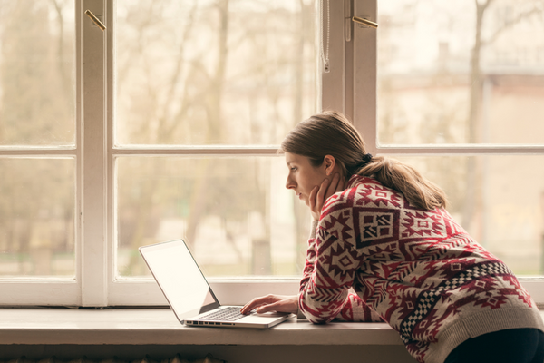 A-woman-in-a-knit-sweater-stands-using-her-MacBook-on-the-window-sill-in-winter