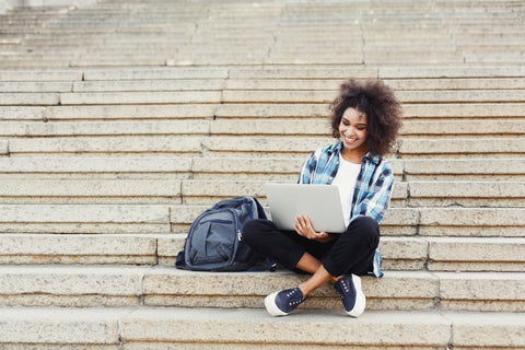 Female-college-student-studying-on-campus-steps-with-a-MacBook