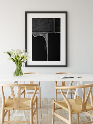Black and white abstract wall print in black frame with white wall