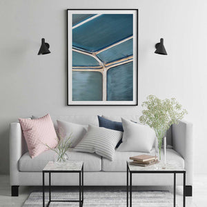 Abstract aerial print in black frame hanging on wall with couch
