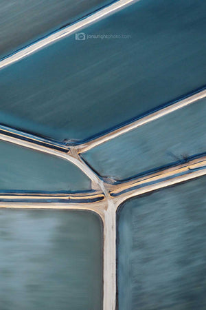 Brushed abstract photography of salt ponds with muted blue tones