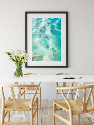 Blue and green print framed in black hanging on the wall