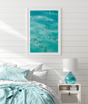 beach print in white frame hanging on wall