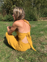 Load image into Gallery viewer, Ethically made Backless, wide leg, halter neck jumpsuit with tie back, back view in gold