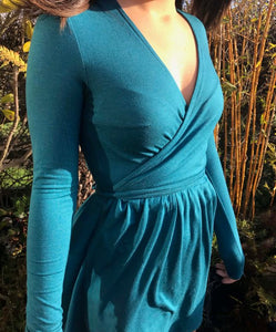 Ethically made stretch wrap mini dress with tie waist and gathered skirt. Teal