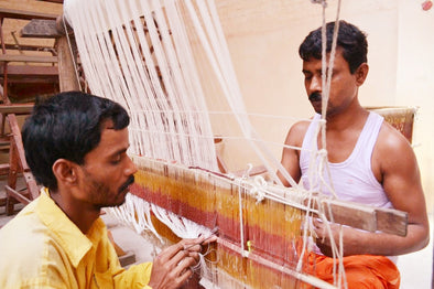 Two artisans setting loom