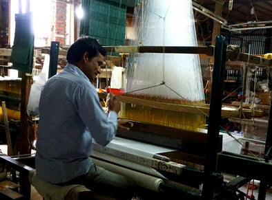 A man weaving in hand loom