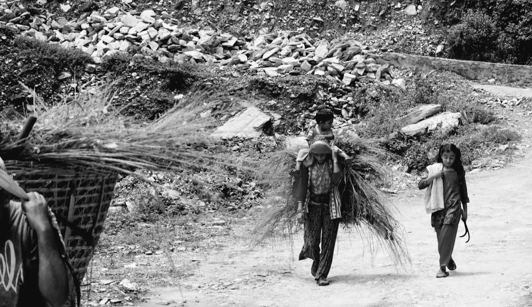 A woman carrying doko and a kid on her back