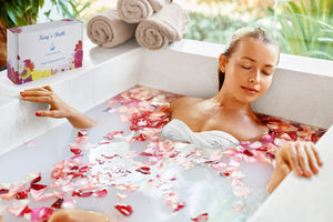 beautiful woman reclining in bath bomb with a box of Kay's Bath bombs