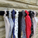 The cutest hair scarf scrunchies are here! We have red, navy, white, black and tan with polka dots and black and white with spotty dots. Such a fun and flirty way to dress up  your pony tail.