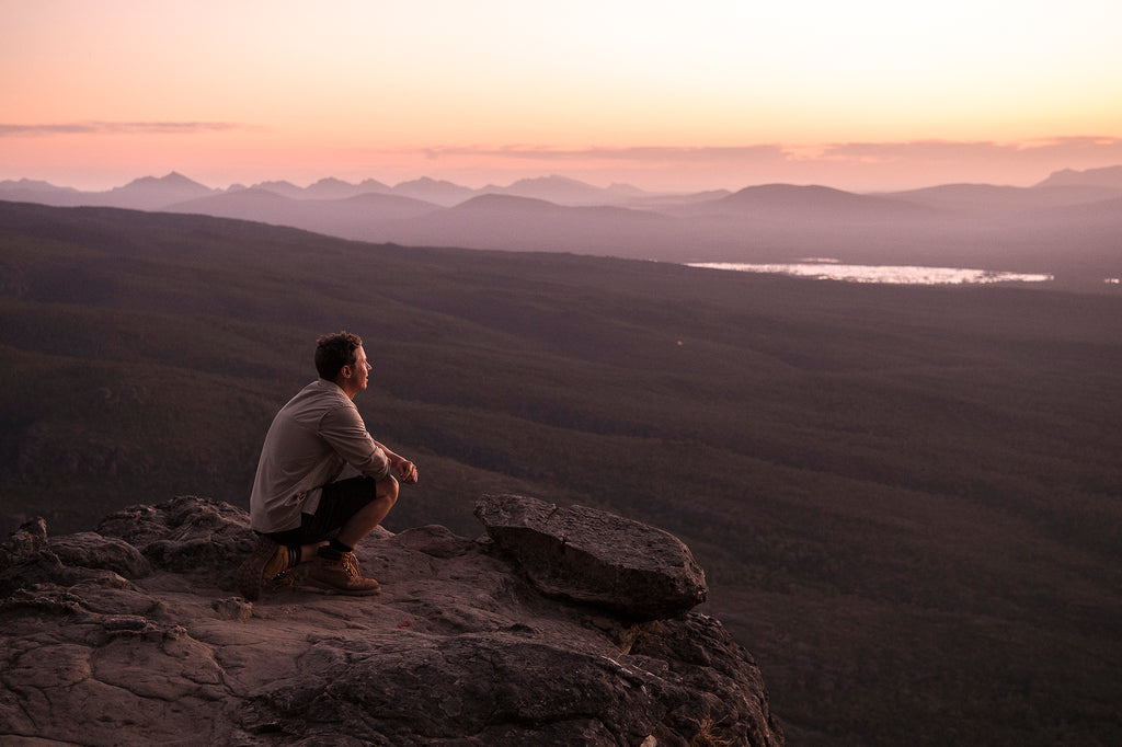 Man on a cliff starting off into the sunset, overlooking a beautiful mountain range