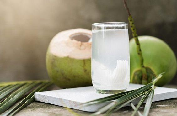 coconut water on marble slab with coconuts in background